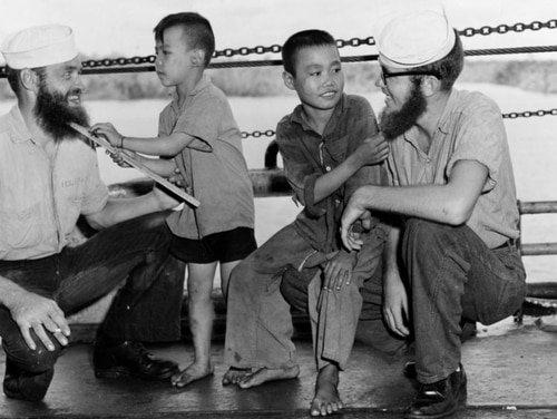 U.S. Navy sailors have their beards inspected by young Vietnamese refugees during the trip from Haiphong to Saigon, during an August 1954 Tonkin Gulf beard-growing competition. Once a staple of the sea service, the Navy has been debating beards for decades. (National Archives)