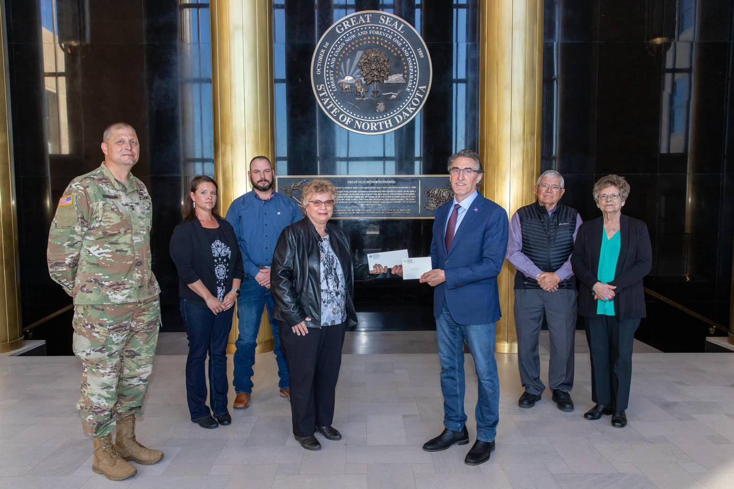 Gov. Doug Burgum presents Ron Hepper's military ID tag to his widow, Ruth Hepper of Bismarck, on Wednesday, Sept. 30, at the Capitol in Bismarck.