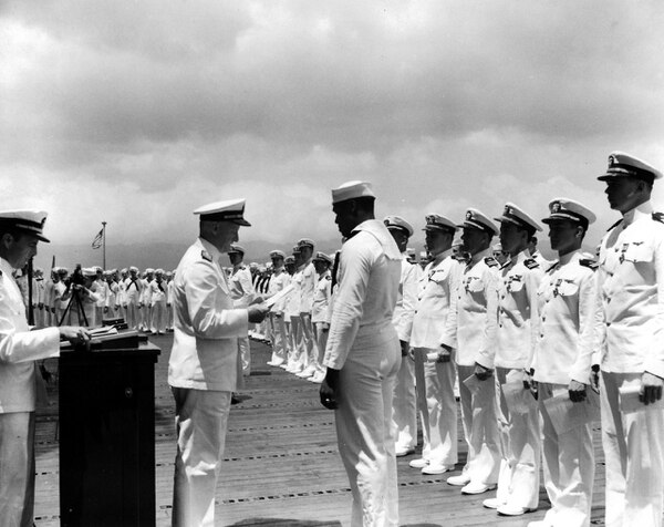 Mess Attendant 2nd Class Doris Miller receives the Navy Cross from Adm. Chester W. Nimitz at a ceremony held on the flight deck of the aircraft carrier Enterprise at Pearl Harbor, 27 May 1942. (National Archives)