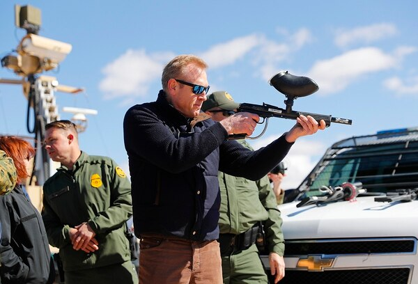 Acting Secretary of Defense Patrick Shanahan, center, fires a modified painted ball gun during a tour of the US-Mexico border at Santa Teresa Station in Sunland Park, N.M., Saturday, Feb. 23, 2019. (Pablo Martinez Monsivais/AP)
