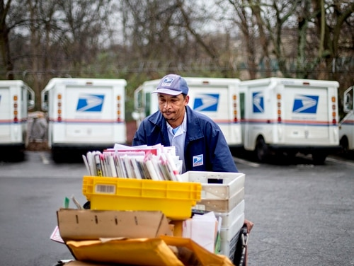 In this Feb. 7, 2013 file photo, U.S. Postal Service letter carrier Michael McDonald gathers mail to load into his truck before making his delivery run in the East Atlanta neighborhood, in Atlanta. After weeks of railing against online shopping giant Amazon, President Donald Trump signed an executive order Thursday, April 12, 2018, creating a task force to study the United States Postal System. (David Goldman/AP)
