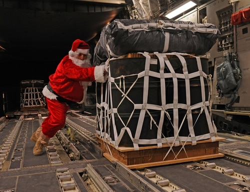 Santa Claus, portrayed by Tech. Sgt. Mike Morris, pushes a pallet of fuel onto a C-17 Globemaster III prior to a mission Dec. 23, 2011. (Staff Sgt. Nathanael Callon/Air Force)