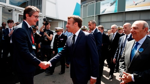 French President Emmanuel Macron shakes hands with Patrice Caine, Chairman and Chief Executive Officer of Aerospace and defence group Thales, as Eric Trappier, Chairman and CEO of Dassault Aviation, looks on during a visit at the 53rd International Paris Air Show at Le Bourget Airport near Paris on June 17, 2019. (Benoit Tessier/AFP via Getty Images)