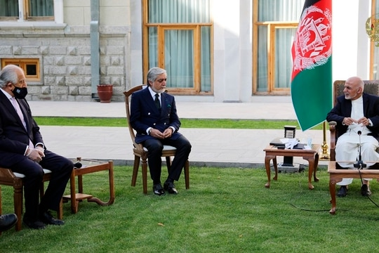 In this May 20, 2020, photo, Afghan President Ashraf Ghani, right, and Abdullah Abdullah, fellow leader under a recently signed power-sharing agreement, center, hold a meeting with U.S. peace envoy Zalmay Khalilzad aimed at resuscitating a U.S.-Taliban peace deal signed in February, at the Presidential Palace, in Kabul, Afghanistan. (The Presidential Palace via AP)