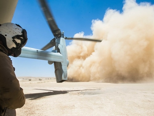 A U.S. Marine Corps crew chief observes an MV-22B Osprey land during a resupply mission in support of Combined Joint Task Force – Operation Inherent Resolve (CJTF-OIR) at Firebase Um Jorais, Iraq, June 27. (Cpl. Jered T. Stone/Marine Corps)