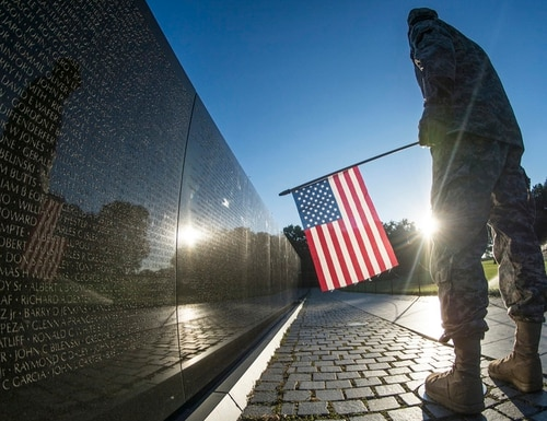 A U.S. Army Reserve soldier reads some of the 58,307 names etched into
