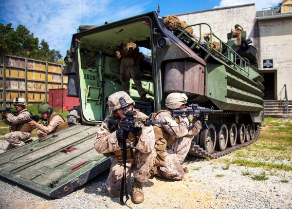 Marines assigned to Battalion Landing Team 3/2, 26th Marine Expeditionary Unit (MEU), provide security during a direct action raid from an amphibious assault vehicle at Fort Pickett, Va., Sept. 8, 2012. AAV's are an essential part of the MEU, their main goal is to transport Marines and Sailors from ship to shore, so they are able to accomplish their objective. This training was part of the 26th MEU's pre-deployment training program. BLT 3/2 is one of the three reinforcements of 26th MEU, which is slated to deploy in 2013. (U.S. Marine Corps photo by Cpl. Christopher Q. Stone)