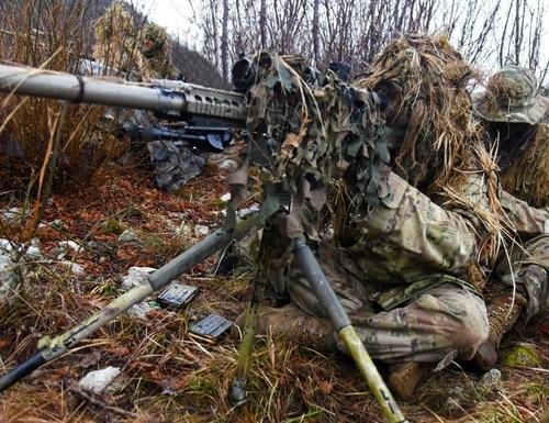A sniper takes aim with a tripod-mounted KAC-built M110 during a training exercise in Europe (Photo US Army)