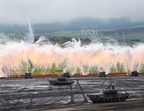 FILE - In this Aug. 18, 2015 file photo, Japan Ground Self-Defense Force's Type-89 armored combat vehicles flare up a smoke screen during an annual live firing exercise at Higashi Fuji range in Gotemba, southwest of Tokyo. In the wee hours of Saturday morning, Sept. 19, 2015, Japan took a step toward having a military in line with most armed forces around the world, one that would be able to take part in combat even when the country is not under direct attack. While Japan's military remains far from unfettered, the package of bills approved by parliament is a further step in a gradual erosion of the restrictions that has been underway for more than two decades. (AP Photo/Shizuo Kambayashi, File)