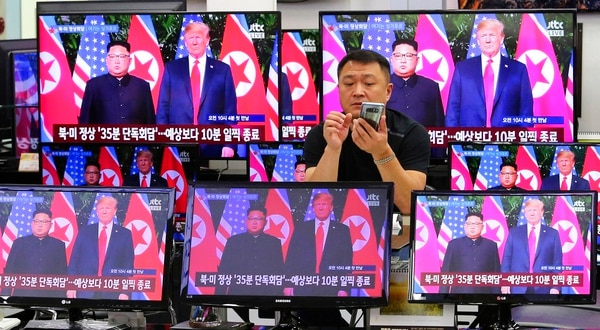 TV screens shows U.S. President Donald Trump, right, meeting with North Korean leader Kim Jong Un in Singapore, during a news program at Yongsan Electronic store in Seoul, South Korea, Tuesday, June 12, 2018. (Ahn Young-joon/AP)