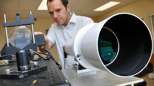 John DeGrassie , Atmospheric Propagation Branch, adjusts the lens on an optical imaging sensor at Space and Naval Warfare Systems Center Pacific (Photo by Alan Antczak/Navy)