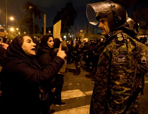 In this Saturday photo, released by the Iranian Students' News Agency, a woman attending a candlelight vigil to remember the victims of the Ukraine plane crash talks to a policeman at the gate of Amri Kabir University in Tehran. Security forces deployed in large numbers across the capital, Tehran, on Sunday, expecting more protests after its Revolutionary Guard admitted to shooting down a passenger plane. (Mona Hoobehfekr/ISNA via AP)
