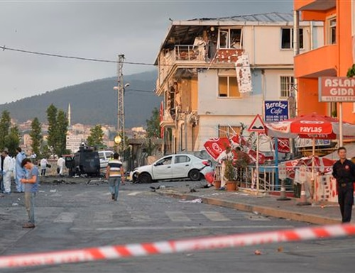 Turkish police officers work near the site of an explosion at a police station, seen right, in Istanbul's Sultanbeyli neighborhood, early Monday, Aug. 10, 2015. The bomb attack at the police station injured three policemen and seven civilians and caused a fire that collapsed part of the three-story building. Police said the assailants exploded a car bomb near the station. Unknown assailants later fired on police inspecting the scene of the explosion, sparking another gunfight with police that killed a member of the police inspection team and two assailants. (AP Photo/Akin Celiktas)