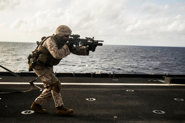 Marine Joseph Burk fires at his target on the move during a short-range marksmanship qualification course aboard the USS Rushmore at sea in the Indian Ocean, June 18, 2015. Burk is a team leader with Kilo Company, Battalion Landing Team 3rd Battalion, 1st Marine Regiment, 15th Marine Expeditionary Unit. The marksmanship course improves Marine's combat shooting tactics and prepares them for future operations while deployed with the 15th MEU. (U.S. Marine Corps photo by Sgt. Emmanuel Ramos/Released)