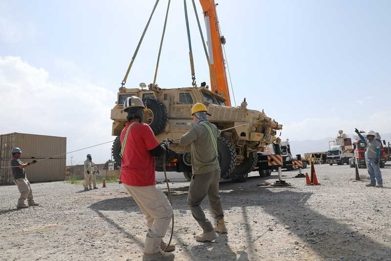 Civilian contractors prepare to load a Mine Resistant Ambush Protected vehicle on to a flatbed trailer during the retrograde cargo operation on Bagram Air Field, Afghanistan, July 12, 2020. (Sgt. 1st Class Core Vandiver/Army)