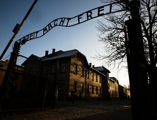 The sun lights the buildings behind the entrance of the former Nazi death camp of Auschwitz-Birkenau in Oswiecim, Poland on Dec. 6. (Markus Schreiber/AP)