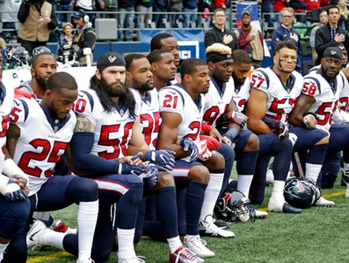 Houston Texans players kneel during the singing of the national anthem before an NFL football game against the Seattle Seahawks on Oct. 29, 2017 in Seattle. (Elaine Thompson/AP)
