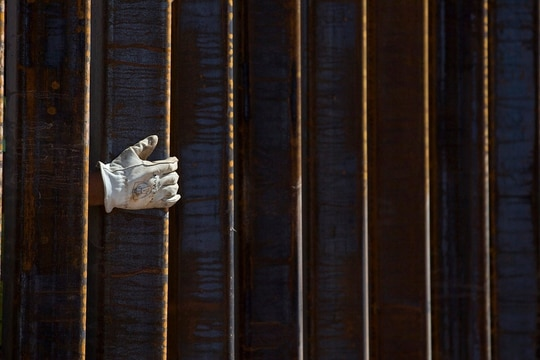 A construction worker's gloved hand is seen through a portion of the 30-foot tall bollard fence on the U.S.-Mexico border. (Mamta Popat/Arizona Daily Star via AP)