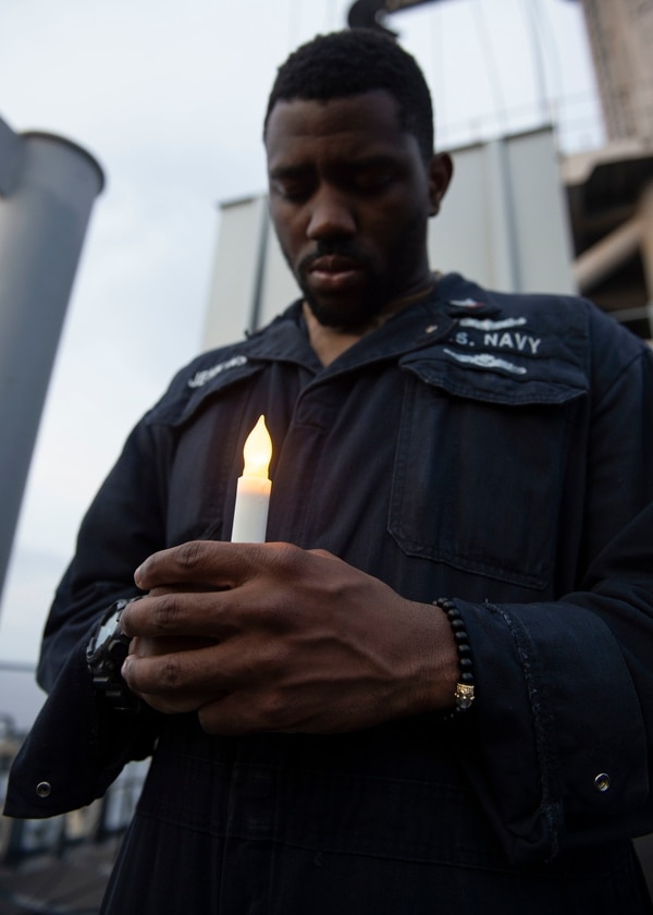 Assigned to the amphibious assault ship Boxer, Religious Programs Specialist 3rd Class Kenon Jenkins bows his head for a moment of silence during a Sept. 28 suicide awareness candlelight vigil on vulture's row. Boxer was operating in the South China Sea. (Mass Communication Specialist 2nd Class David Ortiz/Navy)