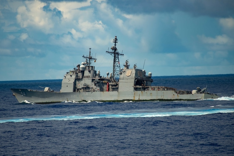 Despite a recent fire on board, the guided-missile cruiser Antietam steams ahead during Tuesday's air power demonstration, taking part in a 5-inch gun shoot. (MCSA Oswald Felix Jr./Navy)