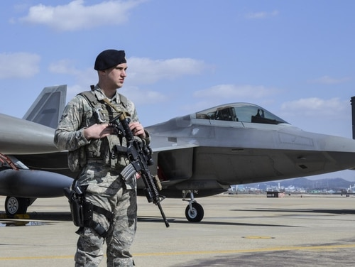 A security forces airman at Osan Air Base in South Korea stands guard next to an F-22 Raptor fighter in February 2016, after it conducted a flyover in response to North Korean actions. The Air Force is restoring re-enlistment bonuses to cryptologic language analysts who speak Korean. (Tech. Sgt. Travis Edwards/Air Force)