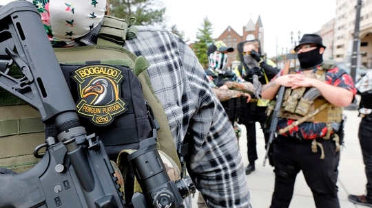 A group tied to the Boogaloo Bois holds a rally as they carry firearms at the Michigan State Capitol in Lansing, Mich., on Oct. 17, 2020. (Jeff Kowalsky/AFP via Getty Images)