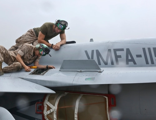 U.S. Marines Lance Cpl. Jordan J. Gomez, bottom, and Lance Cpl. Steve G. Pitkin, both electricians with Marine Fighter Attack Squadron (VMFA) 115, troubleshoot issues with the right engine of a F/A-18 Hornet aircraft at Marine Corps Air Station Beaufort, S.C., May 15, 2014. Daily maintenance is vital to VMFA-115 and their aircraft. (U.S. Marine Corps photo by Lance Cpl. Austin A. Lewis/Released)