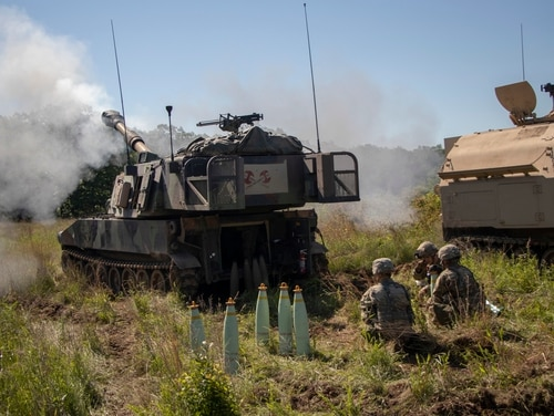 An M109 Paladin crew with 2nd Battalion, 142nd Field Artillery Brigade fires a round during a live-fire exercise during annual training. But this scene will be a relic if the Army can get autoloaders and autonomous resupply problems solved with a new program. (Sgt. Roger Houghton/Army)