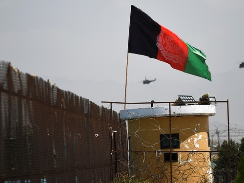 Two helicopters are seen flying past an Afghan national flag during the 100th anniversary of the country's Independence Day in Kabul on Aug. 19, 2019. (Wakil Kohsar/AFP via Getty Images)