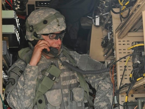 A 2nd Heavy Brigade Combat Team soldier uses a radio from inside a Mine Resistant Ambush Protected vehicle equipped with multiple communication platforms during the Network Integration Evaluation 14.2, May 1. (Staff Sgt. Richard Andrade/Army)
