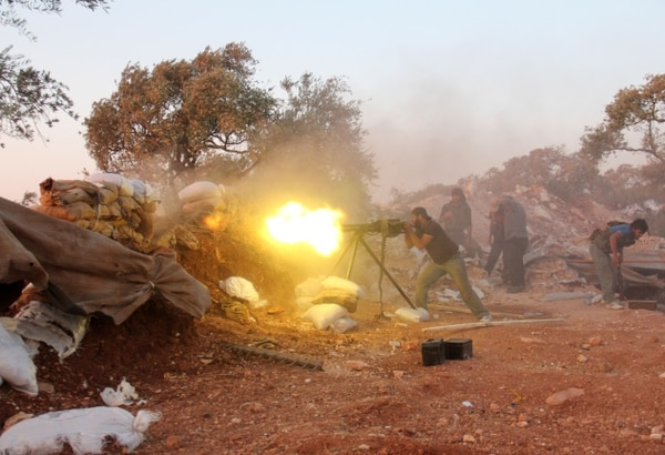 A rebel fighter fires a heavy machine gun during clashes with government forces and pro-regime shabiha militiamen in the outskirts of Syria's northwestern Idlib province in 2015. (Omar Haj Kadour/AFP/Getty Images)