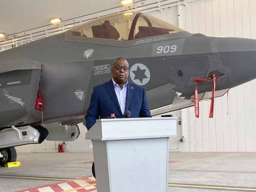 U.S. Defense Secretary Lloyd Austin speaks to reporters at Israel's Nevatim air base Monday, with an Israeli F-35 fighter jet in the background, at Nevatim Israeli Air Force Base, Monday, April 12, 2021 in Israel. (Robert Burns/AP)