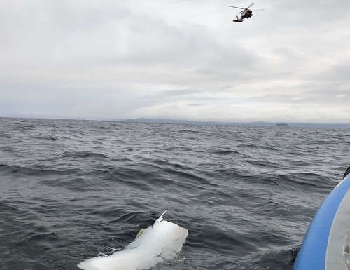 A Coast Guard Air Station Sitka MH-60 Jayhawk rescue helicopter crew flies over a piece of debris spotted by Alaska Wildlife Troopers while searching for three people aboard an overdue Guardian Life Flight aircraft 20-miles west of Kake, Alaska on Jan. 30. (Alaska Wildlife Troopers)