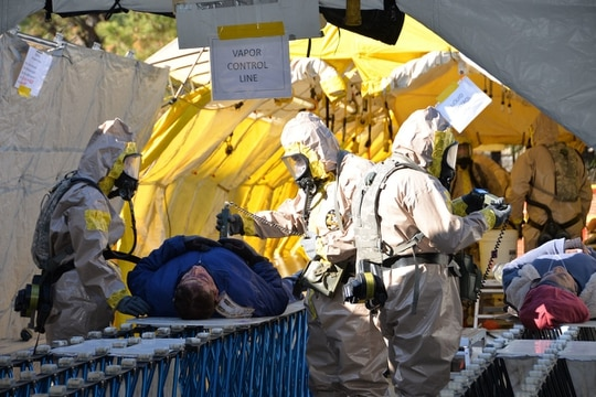 New York Army National Guard soldiers of the Homeland Response Force for FEMA Region 2 move a simulated casualty through decontamination on Nov. 16, 2019, during an exercise for chemical, biological, radiological or nuclear (CBRN) incident response training at Lakehurst Naval Air Station at Joint Base McGuire Dix Lakehurst in Lakehurst, N.J. (Col. Richard Goldenberg/Army National Guard)