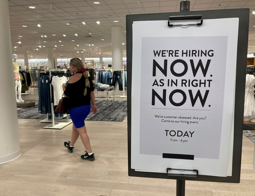 A customer walks behind a sign at a Nordstrom store seeking employees in Coral Gables, Fla., on May 21. (Marta Lavandier/AP)