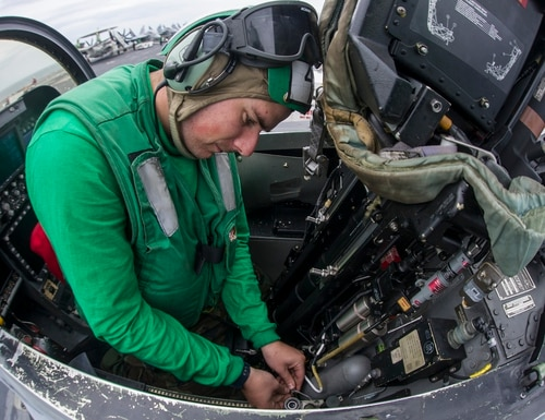 Aviation Structural Mechanic (Safety Equipment) 2nd Class Frank McMahon performs maintenance in the cockpit of an F/A-18E Super Hornet. (MC3 Bryan Mai/Navy)