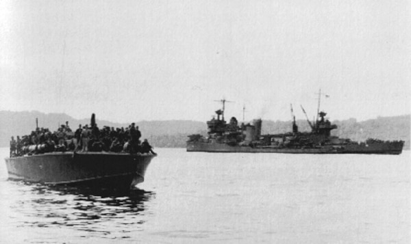 A PT boat bringing survivors of the heavy cruiser Northampton into Tulagi harbor after the Battle of Tassafaronga off Guadalcanal. In the background is the heavy cruiser New Orleans with its bow blown off, including the number 1 main battery turret. New Orleans survived despite losing almost a quarter of its length. (U.S. Naval History and Heritage Command)