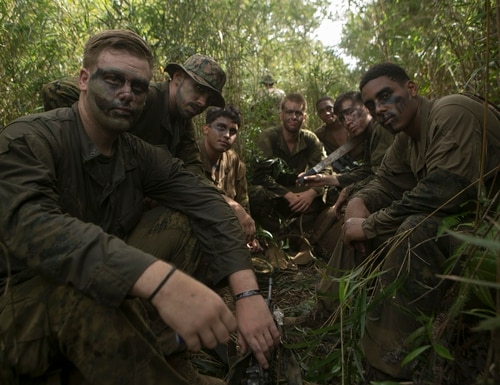 CAMP GONZALVES, OKINAWA, Japan -- Marines with India Company, 3rd Battalion, 3rd Marine Regiment take a break Aug. 3 at the Jungle Warfare Training Center on Okinawa, Japan. As they wait for their resupply for water, they sit in the brush wearing their test Marine Corps combat utility uniforms. The new uniforms and boots are supposed to be lighter and faster to dry. (U.S. Marine Corps photo by Cpl. Tyler Ngiraswei/ Released)