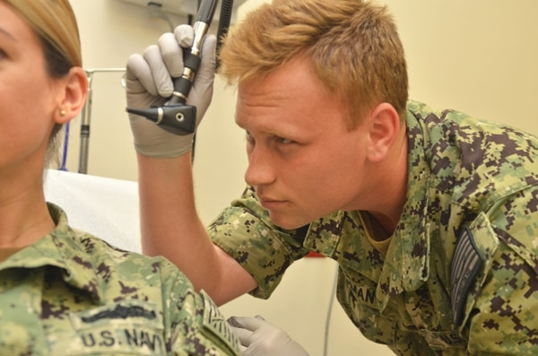 Hospitalman Kevin German checks a patient's ear at Naval Branch Health Clinic Jacksonville's treatment room on Oct. 17. (Jacob Sippel/Navy)