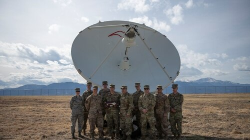Airmen from the 4th Space Control Squadron take a picture in front of the Counter Communications System Block 10.2 on Peterson Air Force Base, Colo. (Airman 1st Class Andrew Bertain/Air Force)