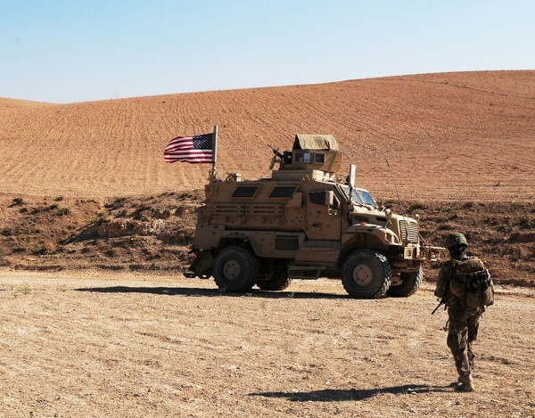 A U.S. soldier walks toward a tactical vehicle used to provide security during an independent, coordinated patrol outside Manbij, Syria, Aug. 19, 2018. These patrols are coordinated with Turkish military forces to ensure the continued safety and security in Manbij. (Sgt. Nicole Paese/Army)