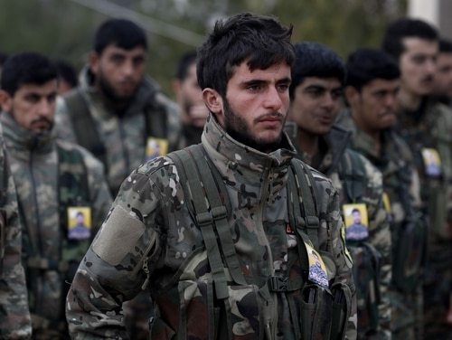 Fighters from the Syrian Democratic Forces attend the funeral of a fellow fighter, who was killed while fighting against the Islamic State group in the northeastern Syrian Kurdish-majority city of Qamishli on Jan. 18, 2019. (Delil Souleiman/AFP via Getty Images)