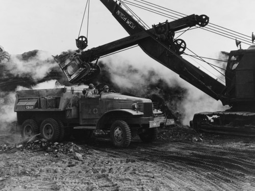 A power shovel lifts volcanic ash and stone, while loading a 62nd Construction Battalion truck amid a steamy Iwo Jima landscape, March 1945. (National Archives)