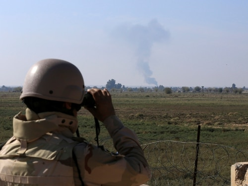 An Iraqi soldier watches smoke rising after an airstrike by U.S.-led coalition warplanes against ISIS, on the border between Syria and Iraq in Qaim, Anbar province, Iraq. (Hadi Mizban/AP)