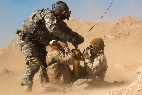 A flight medic hooks a hoist to a jungle penetrator carrying two Marines during a casualty evacuation exercise Feb. 5, 2015, near Camp Buehring, Kuwait. (Minnesota Army National Guard photo by Spc. Jess Nemec/Marine Corps)
