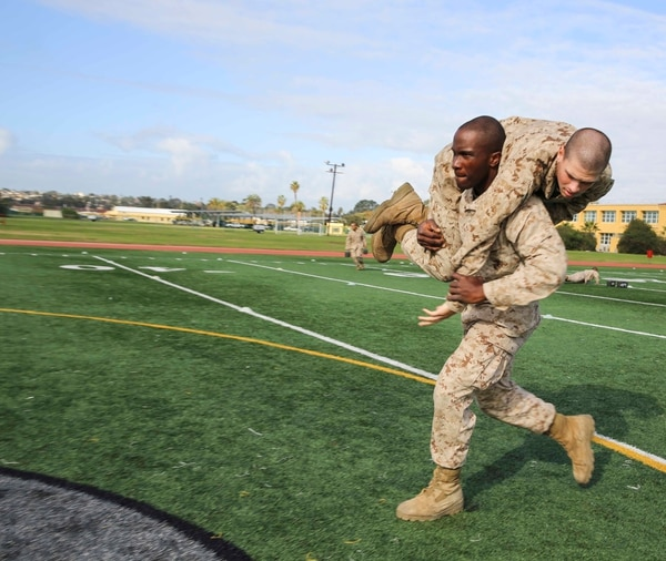 San Diego, California - Private First Class Kanayochukwu Onyejeli, Platoon 3235, Kilo Company, 3rd Recruit Training Battalion, conducts the fireman carry during the maneuver under fire portion of the Combat Fitness Test at Marine Corps Recruit Depot San Diego, Calif., Dec. 22. The event consists of an 880-yard run, timed 30-pound ammunition can lifts and a maneuver under fire drill. (Cpl. Jericho Crutcher/Marine Corps)
