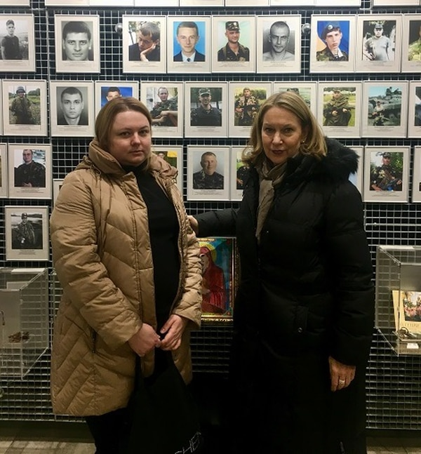 """A young widow of a Ukrainian soldier shows Bonnie Carroll a photo of her husband at the Ukrainian museum of """"The Civilian Endeavor of the People of Dnipropetrovsk Oblast"""