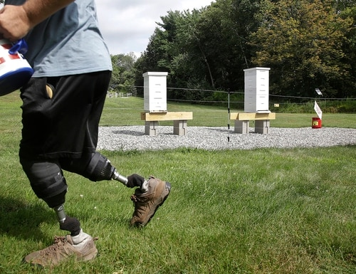 In this Aug. 7, 2019, photo, U.S. Army veteran Oscar Toce cleans up after beekeeping at the Veterans Affairs' beehives in Manchester, N.H. (Elise Amendola/AP)