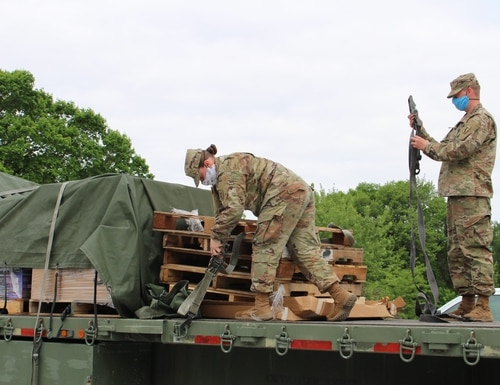 Nebraska Army National Guard soldiers secure cargo after delivering essential supplies to a mobile testing site at the Seward County Fairgrounds in Seward, Neb., May 27, 2020. (Staff Sgt. Heidi McClintock/Nebraska National Guard)