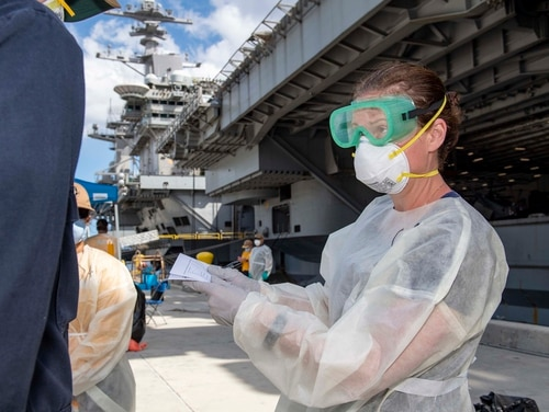 Cmdr. Brianna Rupp, a preventative medicine physician from the Navy and Marine Corps Public Health Center, takes a survey from a U.S. sailor assigned to the aircraft carrier Theodore Roosevelt on April 22, 2020, in Apra, Guam, as part of a public health outbreak investigation. (MC1 Chris Liaghat/Navy)
